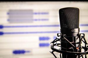 Mikrofon mit Audio-Software im Hintergrund.